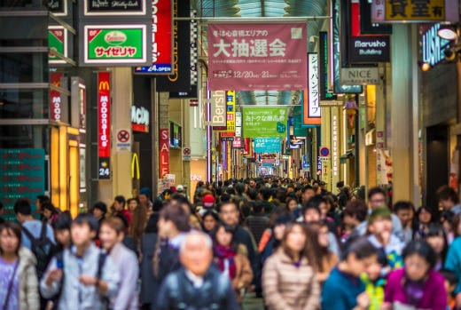 A large group of people walking down a city street in Japan